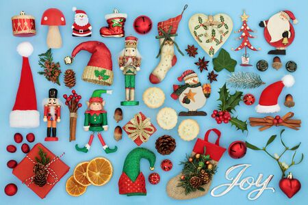 Symbols of Christmas with silver joy sign, retro bauble tree decorations, flora and food selection on pastel blue background Traditional symbols for the festive season. Banque d'images