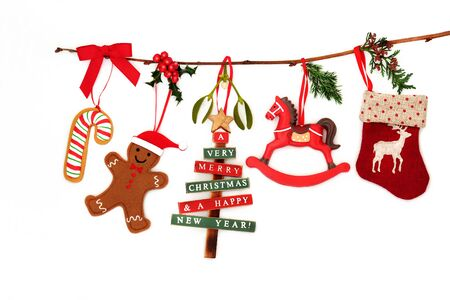 Christmas decorations hanging on a branch with stocking, tree, rocking horse, gingerbread man, candy cane and winter flora on white background with copy space.