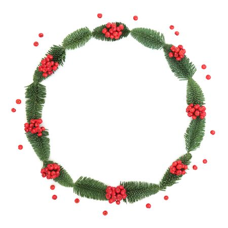 Winter and Christmas holly berry and spruce fir wreath with loose berries on white background with copy space. Traditional symbol for the festive season.