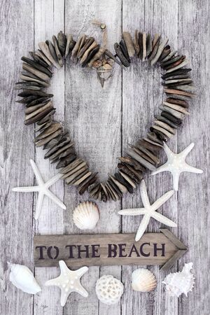 Driftwood heart with to the beach sign with seashells on rustic wood
