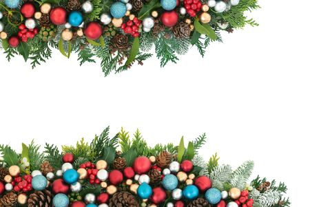 Festive Christmas background border with red, blue and silver ball bauble decorations and winter flora with pine cones on white with copy space.