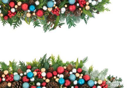 Festliche Weihnachtshintergrundgrenze mit roten, blauen und silbernen Kugelkugeldekorationen und Winterflora mit Kiefernkegeln auf Weiß mit Kopienraum.