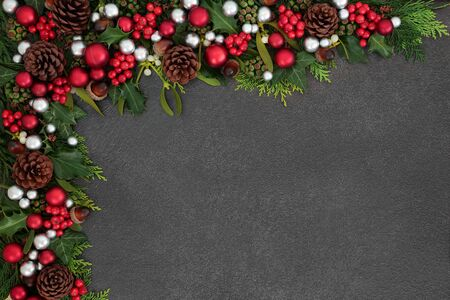 Christmas festive background border with red and silver ball baubles, holly, mistletoe and winter flora on grunge grey background with copy space.