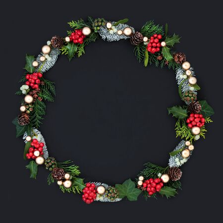 Christmas wreath with winter flora and fauna  and gold bauble decorations on dark grey background with copy space. Traditional festive theme.