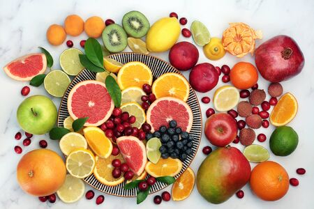 Large healthy fresh fruit collection on a round plate and marble background. Super food very high in antioxidants, vitamins, dietary fibre and anthocyanins. Top view.