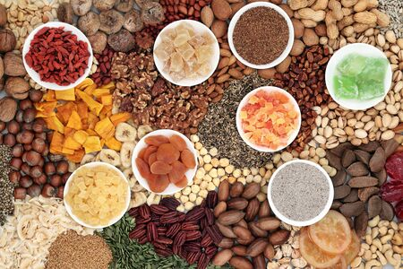 Dried fruit nuts and seed variety forming a background. Health food high in antioxidants, protein, omega 3. minerals, vitamins and anthocyanins. Flat lay. Фото со стока