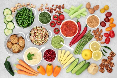 Health food for a vegan diet with falafel meatball substitute, fruit, vegetables, seeds, nuts & dips. High in vitamins, minerals, antioxidants, anthocyanins, protein, fibre, omega 3 & smart carbs. Flat lay. Imagens