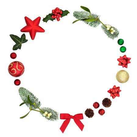 Abstract christmas wreath decoration with baubles, winter flora and traditional symbols on white background with copy space.
