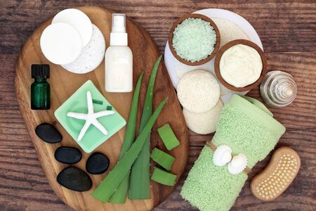 Aloe vera skin care and spa beauty treatment with cosmetic products on olive wood and oak. Soothes sunburn, has anti inflammatory properties, heals skin infections & wounds. Flat lay.