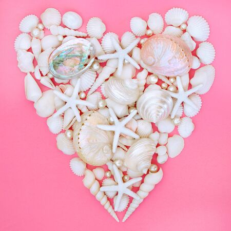 Seashell, starfish and pearl heart with a variety of white shells on pastel pink background,. Romantic valentines day or female baby theme.