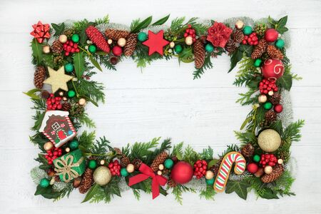 Festive Christmas background border with bauble decorations, holly, mistletoe and winter flora on rustic white wood background with copy space.
