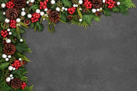 Decorative Christmas background border with silver ball baubles, holly, mistletoe and winter flora with pine cones on grunge grey background with copy space. Standard-Bild