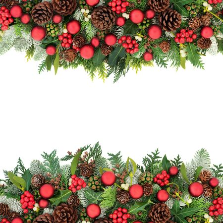 Festive Christmas background border with red bauble decorations and winter holly and winter flora on white background  with copy space. Reklamní fotografie