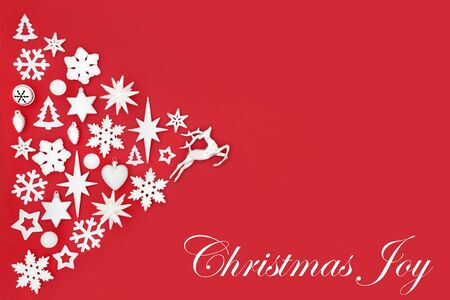 Christmas joy abstract background with white and silver tree decorations and symbols on red with copy space. Traditional theme for the festive season.