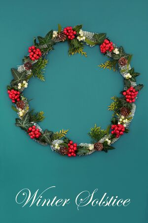 Natural winter solstice wreath with holly, mistletoe, ivy, cedar and snow covered spruce fir on blue green background with copy space. Traditional symbol for the festive season.