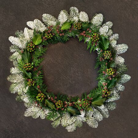 Natural winter and Christmas wreath with snow covered fir, ivy, and cedar leaves on brown gurnge background. Reklamní fotografie