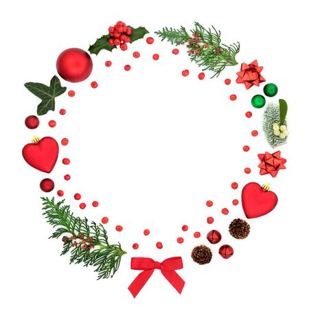 Abstract christmas wreath decoration with baubles, winter flora, loose berries and symbols on white background with copy space. Festive concept for the holiday season.