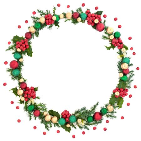 Christmas wreath abstract decoration with winter flora, baubles and loose holly berries on white background with copy space. Decorative symbol for the festive season.