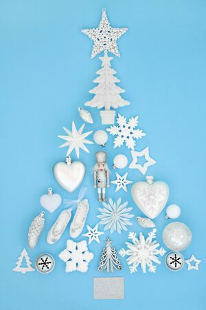 Christmas tree abstract decoration with frosted white and silver baubles and ornaments on pastel blue background. Abstract theme with symbols for the festive season. Stock Photo
