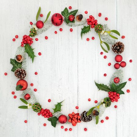 Christmas wreath decoration with loose holly berries and winter flora on rustic wood background with copy space.