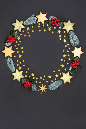 Christmas wreath abstract decoration with gold stars and baubles, holly and winter flora on dark grey background with copy space. Decorative symbol for the festive season.