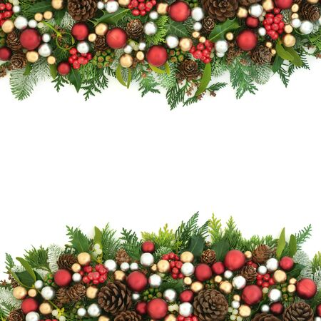 Christmas background border with red, silver and gold bauble decorations and winter flora with pine cones on white with copy space. Stock Photo