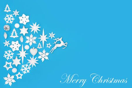 Merry Christmas abstract background with white and silver tree decorations and symbols on blue with title and copy space. Traditional theme for the festive season.