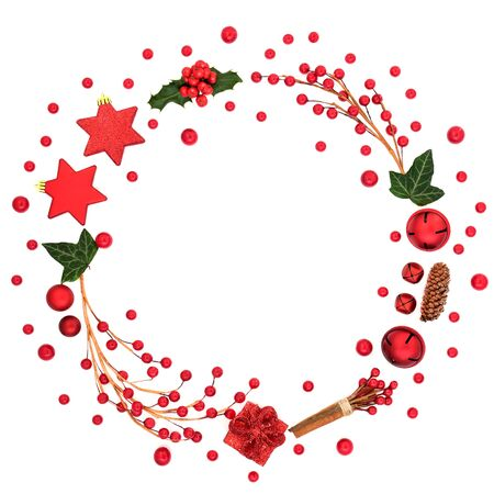 Abstract Christmas & winter wreath decoration with red bauble decorations, berry sprays, holly & winter flora on white background with copy space. Decorative symbol for the festive season. Фото со стока