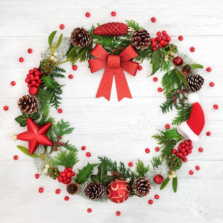 Christmas wreath with red bow, bauble decorations, winter flora and loose holly berries on rustic wood background.