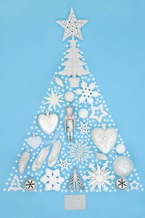 Christmas tree abstract decoration with frosted white and silver baubles, ornaments and snow on pastel blue background. Traditional theme with symbols for the festive season.