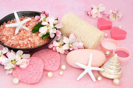 Vegan beauty treatment for skincare with ex foliation himalayan mineral salts, cleansing products & apple blossom flowers on pink background with decorative seashells & pearls. Stock Photo