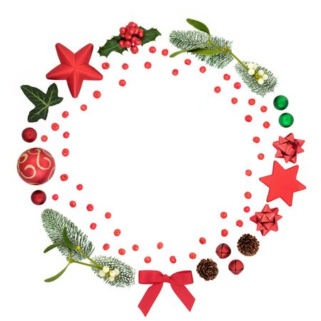Christmas wreath abstract decoration with loose holly berries, winter flora, symbols and baubles on white background with copy space. Decorative symbol for the festive season.