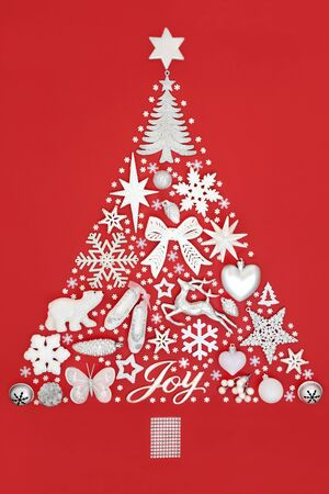 Abstract Christmas tree decoration with silver joy sign & white baubles & ornaments on red background. Traditional theme with symbols for the festive season. Stock Photo