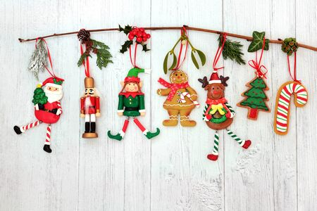 Christmas decorations hanging on a branch with santa claus, tree, reindeer, elf, nutcracker, candy cane & winter flora on rustic wood background with copy space.