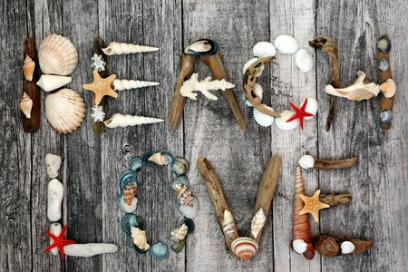 Abstract of driftwood, seashells and pebbles forming the word beach love on rustic wood background. Summer holiday theme. Flat lay. Zdjęcie Seryjne
