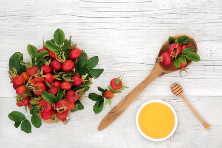 Rosehip red berry fruit health food used in herbal medicine for cold & flu remedy drink with honey. Super food very high in antioxidants & vitamin c. On rustic wood background. Standard-Bild