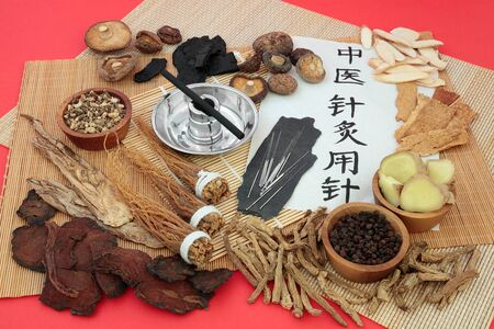 Chinese herbal medicine with herbs used as a tonic, acupuncture needles, moxa stick & script on rice paper. Translation reads as acupuncture needles used in traditional Chinese medicine. Stock Photo