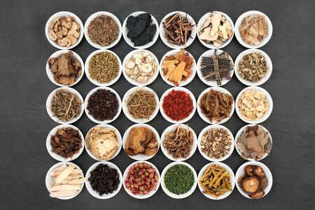 Traditional Chinese herb collection used in herbal medicine in white porcelain bowls on slate background.