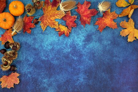 Autumn abstract background border composition with food,flowers and leaves on mottled blue grunge background. Top view. Harvest festival or Halloween theme.