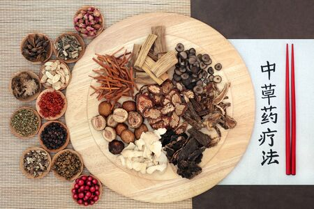 Traditional Chinese herbs used in herbal medicine on a wooden board, bamboo & lotka paper with chopsticks & chinese calligraphy script. Translation reads as traditional Chinese herbal therapy. Banque d'images