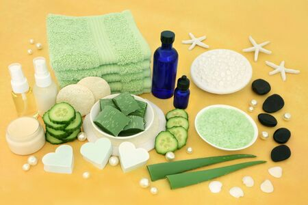 Natural spa skincare beauty treatment with aloe vera and cucumber, spa stones, aromatherapy essential oils, exfoliation and cleansing products on yellow background. Banque d'images