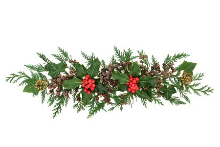 Decorative abstract Winter Christmas & New Year display with holly & loose red berries, ivy & cedar cypress leaves on white background. Natural composition for the festive season. Flat lay, top view. Stock Photo