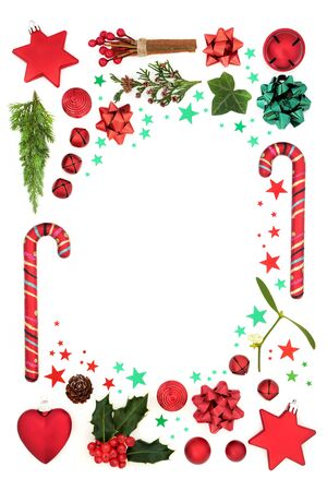 Christmas decorative background border with red bauble decorations, stars, holly, mistletoe & winter greenery on white. Xmas & festive composition. Flat lay, top view, copy space.