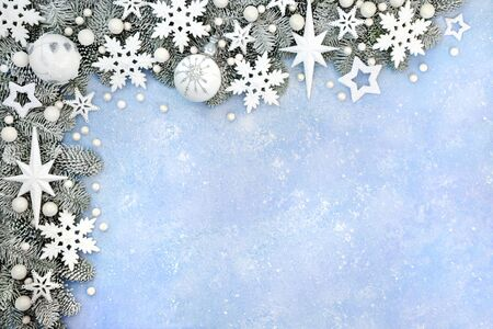 Christmas snow covered border with white star, snowflake & ball bauble decorations on pastel blue background. Xmas & winter & New Year composition for the festive holiday season. Top view, flat lay, copy space.