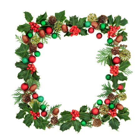 Square Christmas wreath decoration with holly, red & green bauble decorations & winter greenery on white background. Decorative abstract border for the festive season.