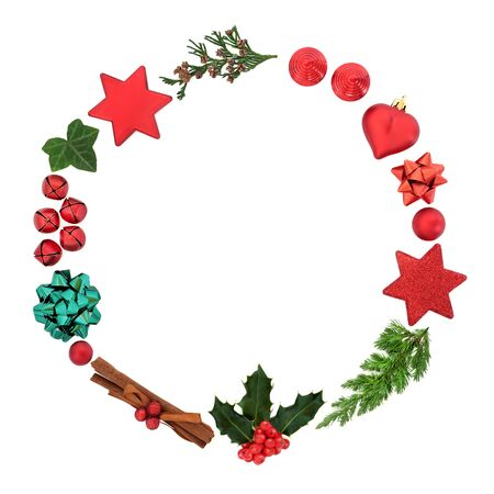 Christmas wreath decoration with winter holly, cedar & fir with red bauble decorations, cinnamon spice & gift bows on white background. Minimal symbol for the xmas season. Top view, flat lay, copy space.