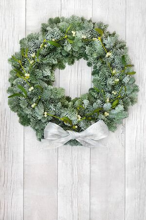 Snow covered spruce fir & mistletoe winter wreath with whiite bow on rustic wood front door background. Composition for solstice, Christmas & New Year. Copy space.
