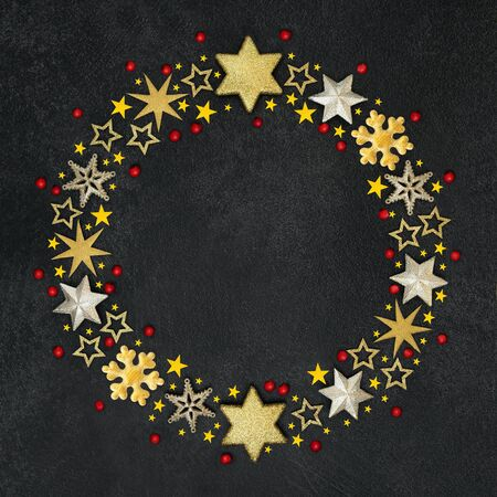 Christmas gold star, snowflake and red holly berry wreath decoration on grunge grey