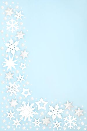 Abstract Christmas star & snowflake background border on pastel blue. Winter, xmas & New Year composition for the festive season. Flat lay, top view, copy space.