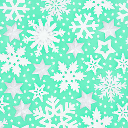 Winter & Christmas snowflake & silver star background pattern on pastel green. Festive composition for Xmas & New Year holiday season. Top view, flat lay.